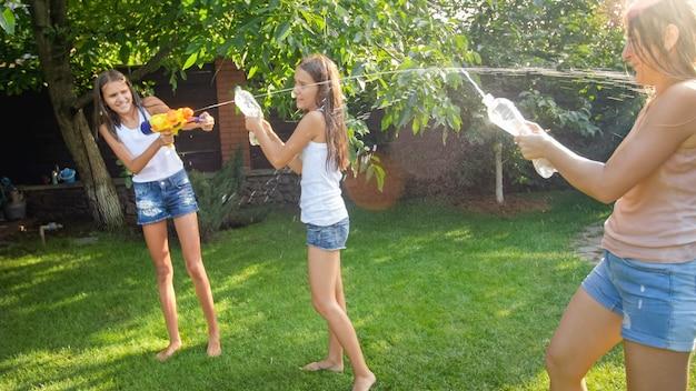Obraz szczęśliwych dzieci bawiących się w przydomowym ogrodzie z pistoletami na wodę i wężem ogrodowym. rodzinna zabawa i zabawa na świeżym powietrzu latem