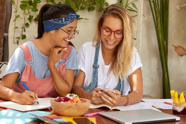 Obraz szczęśliwych uczniów rasy mieszanej komunikuje się podczas procesu e-learningu