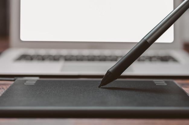 Obraz tabletu graficznego, rysika i laptopa na drewnianym stole. miejsce pracy projektanta. wolny zawód. retusz. koncepcja it.
