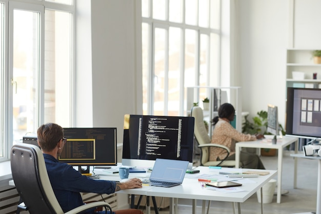 Obraz tła biura programistów it z naciskiem na programistę płci męskiej piszącego kod na ekranie komputera, kopiując przestrzeń