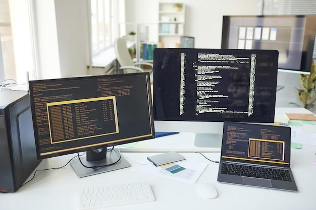 Obraz tła kilku ekranów komputerowych z liniami kodu na biurku w biurze programistów it, miejsce kopiowania
