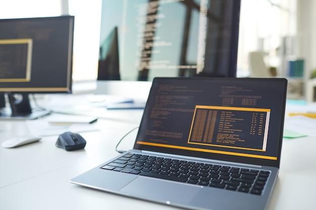 Obraz tła otwartego laptopa z kodem na ekranie przy biurku w biurze programistów it, miejsce kopiowania