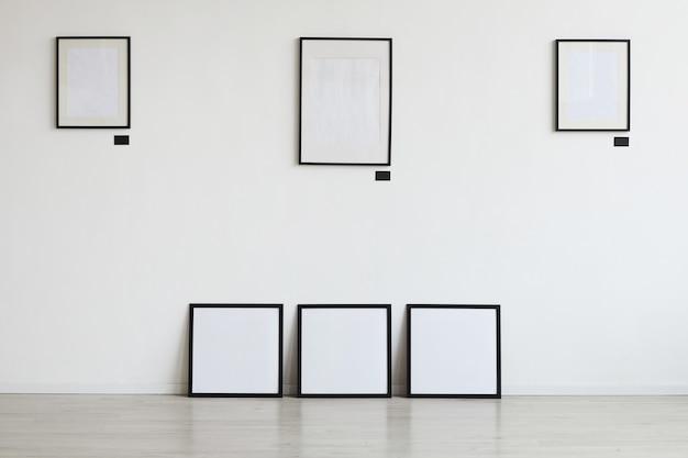 Obraz tła pustych czarnych ramek wiszących na białej ścianie w galerii sztuki,