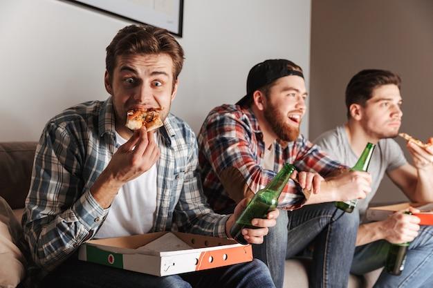 Obraz trzech głodnych facetów, którzy z przyjemnością jedzą pizzę, uważnie oglądając mecz w domu
