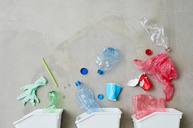 Obraz trzech pojemników na śmieci z posortowanymi śmieciami na białym tle na szarym tle