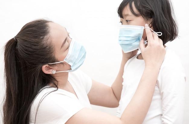 Obraz twarzy młodej azjatki i rodziny noszących maskę, aby zapobiec zarazkom, toksycznym oparom i kurzowi. zapobieganie infekcji bakteryjnej wirus koronowy lub covid 19
