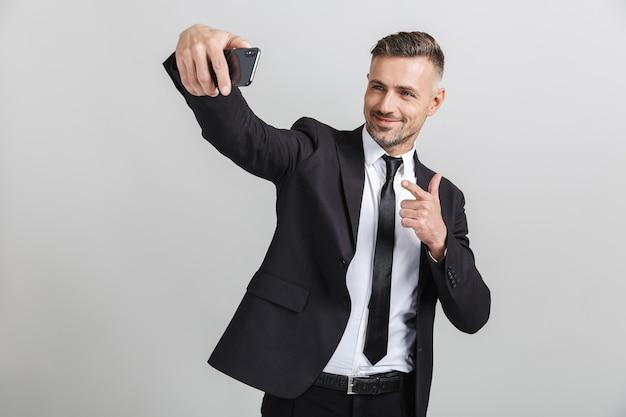 Obraz udanego kaukaskiego biznesmena w formalnym garniturze, wskazując palcem i biorącego selfie na telefon komórkowy na białym tle