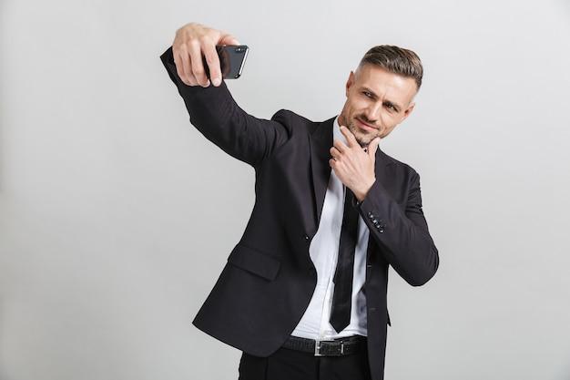 Obraz udanego, pewnego biznesmena w formalnym garniturze dotykającego jego twarzy podczas robienia selfie na telefonie komórkowym na białym tle