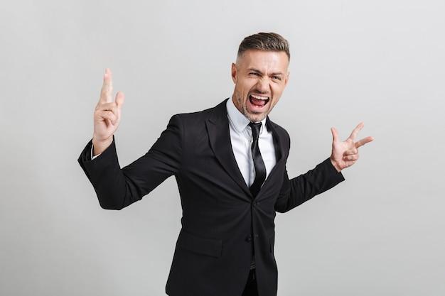 Obraz udanego podekscytowanego biznesmena w formalnym garniturze, krzyczącego i gestykulującego śpiewem pokoju na białym tle