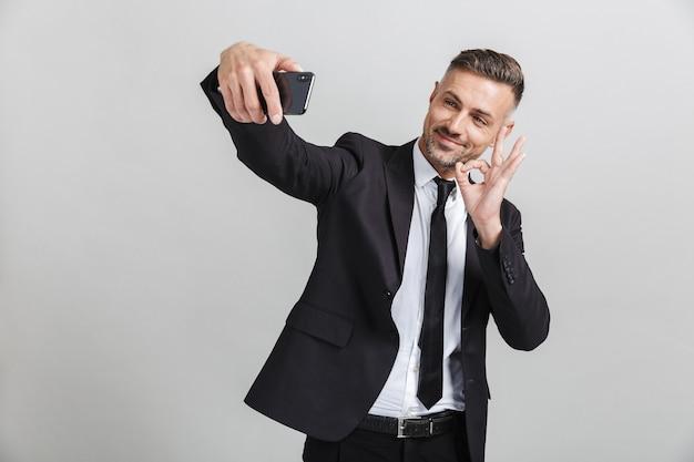 Obraz udanego uśmiechniętego biznesmena w formalnym garniturze, gestykulującego ok śpiewać podczas robienia selfie na telefonie komórkowym na białym tle