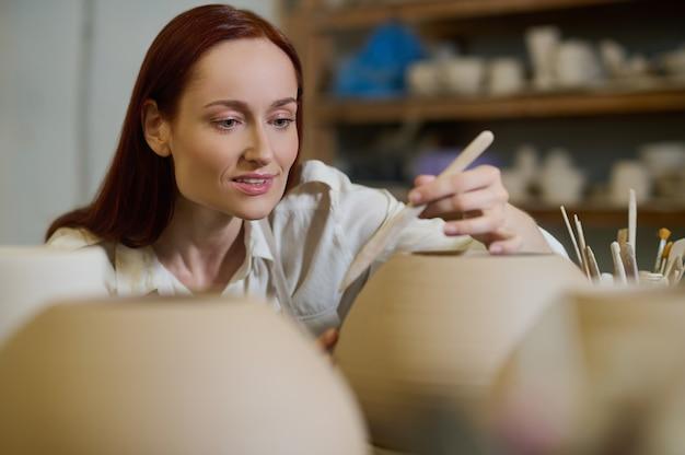 Obraz. urocza kobieta garncarz wygląda na zaangażowaną podczas malowania doniczki