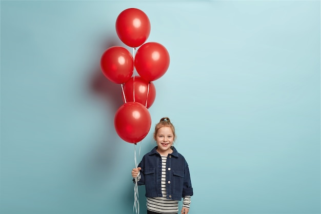 Obraz uroczego małego dziecka w modnej dżinsowej kurtce stoi z czerwonymi balonami, przychodzi na urodziny przyjaciela, ma szczęśliwy wyraz twarzy, stoi nad niebieską ścianą. koncepcja dzieciństwa i świętowania