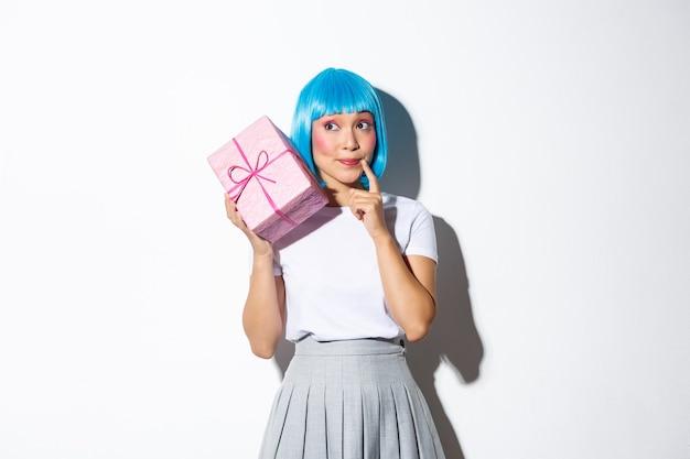 Obraz uroczej azjatyckiej dziewczyny otrzymuje prezent w pudełku na wakacje, wygląda zaciekawiony, próbuje odgadnąć, co jest w środku, stoi.