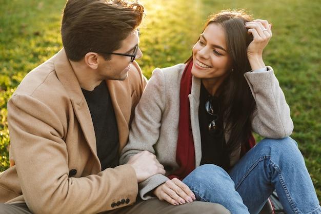 Obraz uroczej europejskiej pary mężczyzny i kobiety w wieku 20 lat, przytulających się i patrzących na siebie, siedząc na trawie w parku