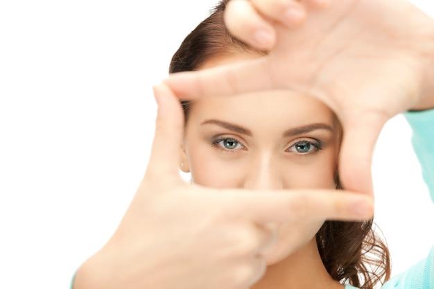 Obraz uroczej kobiety tworzącej ramkę palcami