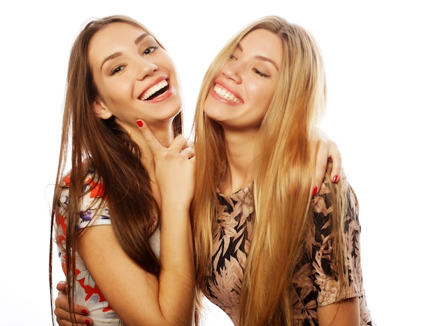 Obraz uroczych przyjaciółek młodych dziewczyn w kolorowej sukience na białym tle