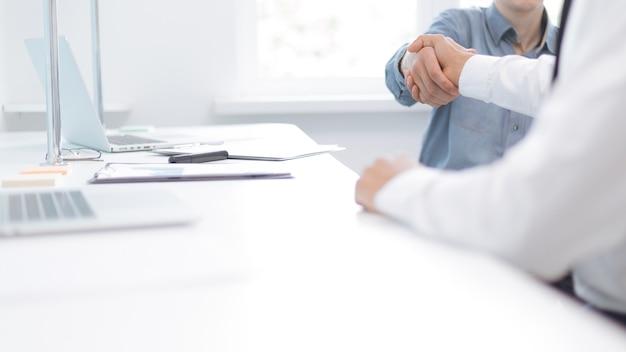 Obraz uścisku dłoni ludzi biznesu w pobliżu pulpitu. zdjęcie z miejscem na kopię.