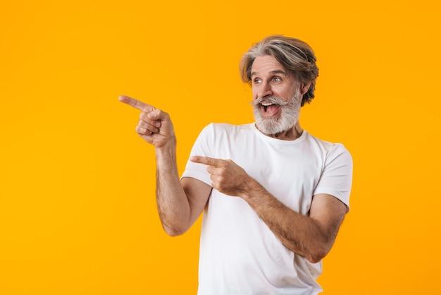 Obraz uśmiechający się starszy siwy brodaty mężczyzna pozowanie na białym tle na żółtej ścianie wskazując.