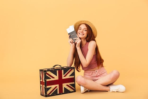 Obraz uśmiechnięta młoda piękna ruda kobieta pozuje na białym tle nad żółtą ścianą, trzymając walizkę i paszport z biletami.