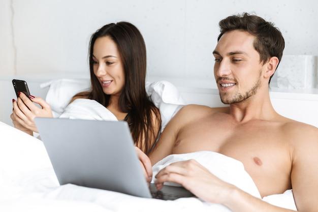 Obraz uśmiechnięta para za pomocą laptopa i smartfona, leżąc w łóżku w domu lub w hotelu