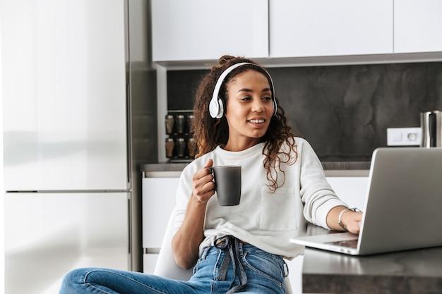 Obraz uśmiechnięte african american girl noszenie słuchawek za pomocą laptopa, siedząc w jasnej kuchni