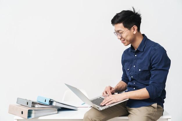 Obraz uśmiechniętego chińczyka w okularach siedzącego przy stole i pracującego na laptopie w biurze na białym tle nad białą ścianą