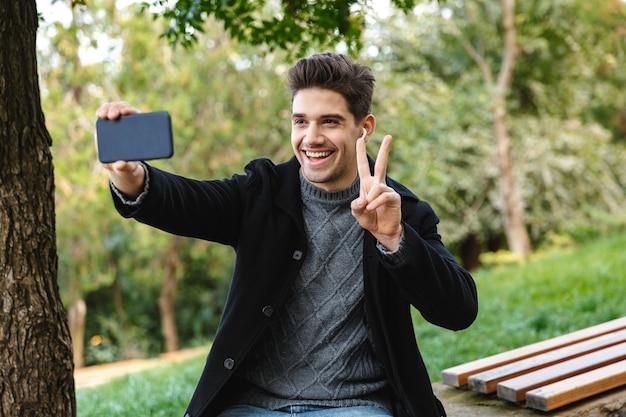 Obraz uśmiechniętego optymistycznego młodego mężczyzny w swobodnym ubraniu spacerującym na świeżym powietrzu w zielonym parku za pomocą telefonu komórkowego weź selfie z gestem pokoju.