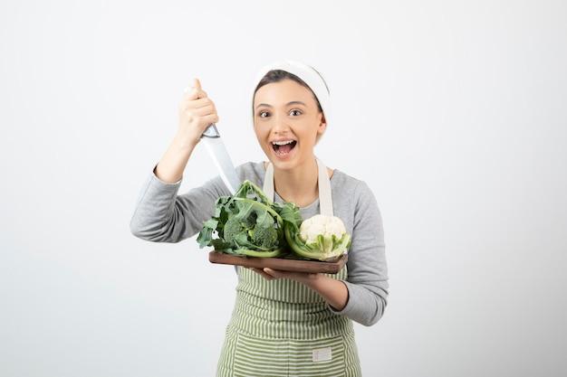 Obraz uśmiechniętej atrakcyjnej kobiety trzymającej nóż z drewnianym talerzem kalafiorów