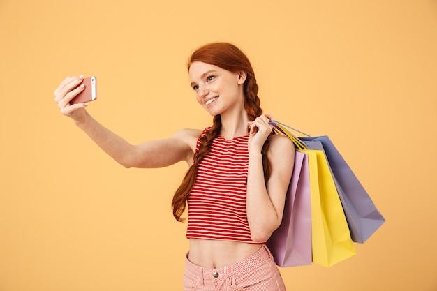 Obraz uśmiechniętej młodej ładnej rudej kobiety pozuje na białym tle nad żółtą ścianą trzymając torby na zakupy weź selfie przez telefon komórkowy.