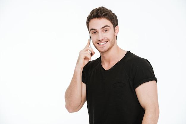 Obraz uśmiechnięty młody człowiek ubrany w czarny t-shirt stojący na białym tle rozmawia przez telefon.