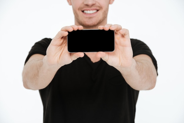 Obraz uśmiechnięty młody mężczyzna ubrany w czarny t-shirt stojący na białym tle pokazujący wyświetlacz jego telefonu do kamery.