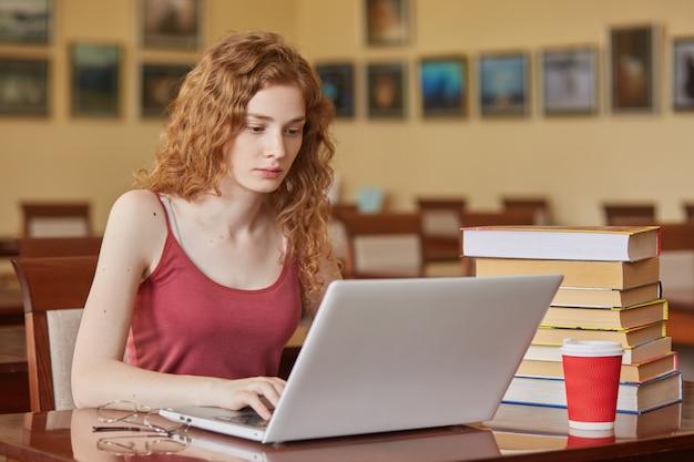 Obraz uważnej, przemyślanej młodej dziewczyny, która pracuje na swoim laptopie w bibliotece, odkłada okulary i kubek napoju, szuka informacji, pisze artykuł, ma dodatkową literaturę przy biurku.