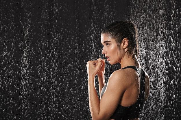 Obraz w prifile mokrej uroczej kobiety boks i stojący w pozycji obronnej pod kroplami deszczu, odizolowane na czarnym tle