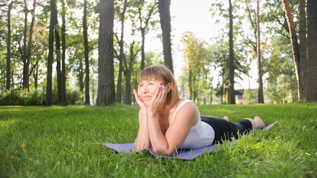Obraz w średnim wieku uśmiechnięta szczęśliwa kobieta medytuje i robi ćwiczenia jogi na trawie w lesie. kobieta dbająca o zdrowie fizyczne i psychiczne podczas ćwiczeń fitness i rozciągania w parku