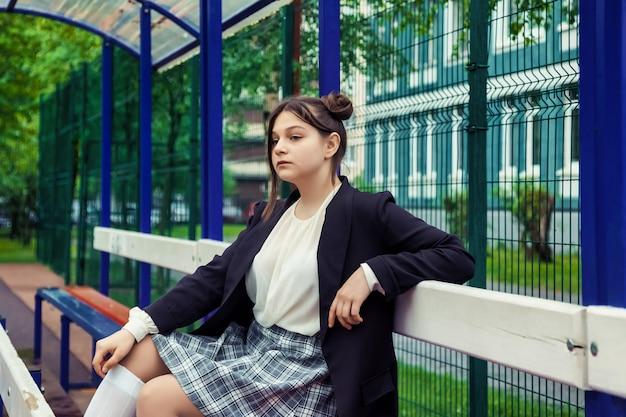Obraz w stylu filmu art noise. portret trzynastoletniej uczennicy w białej bluzce, spódnicy w kratę i kurtce w szkole. emocjonalne teen dziewczyna pozuje patrząc na kamery. pojęcie wieku szkolnego i uczenia się
