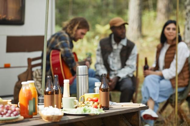 Obraz w tle drewnianego stołu piknikowego z butelkami piwa i jedzeniem na kempingu przyczepy kempingowej