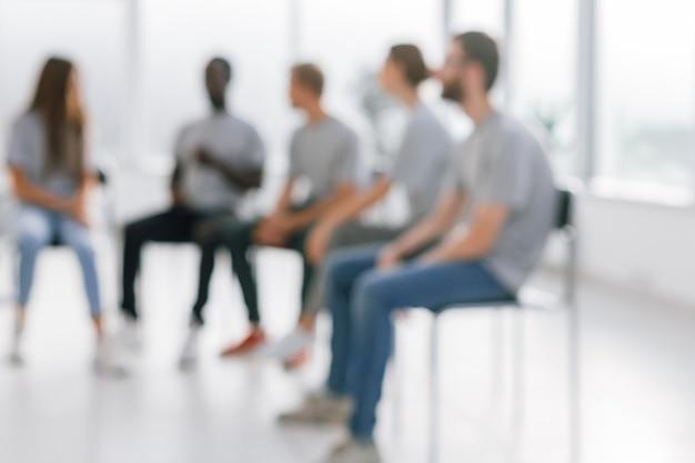 Obraz w tle grupy młodych ludzi siedzących w kręgu. zdjęcie z miejscem na kopię
