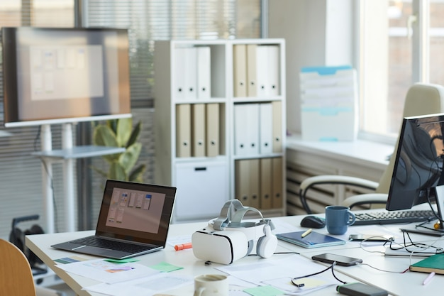 Obraz w tle niechlujnej sali konferencyjnej w biurze programistów it z komputerami i zestawem słuchawkowym vr na stole, miejsce na kopię