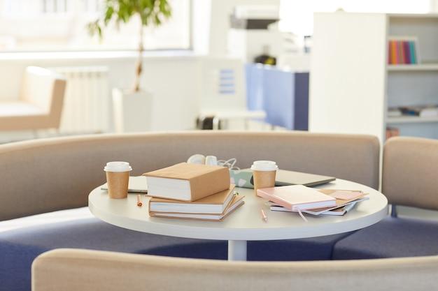 Obraz w tle okrągłego stołu w bibliotece z materiałami do nauki udekorowanymi papierem rzemieślniczym,