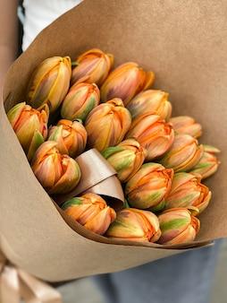 Obraz w tle pięknych kwiatów w zbliżeniu. bukiet pomarańczowych tulipanów o niezwykłej różnorodności w papierze rzemieślniczym na luksusowy prezent na wakacje. delikatne rośliny w kwiaciarni