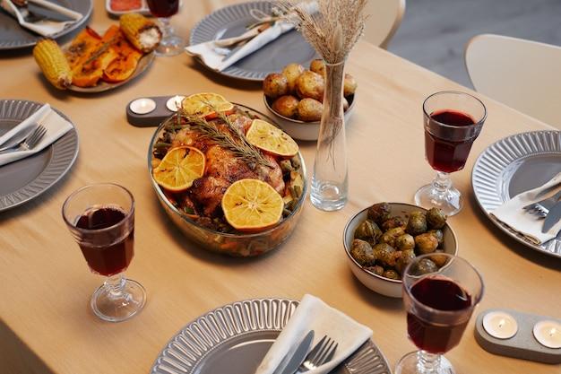 Obraz w tle pysznego kurczaka pieczonego przy stole w święto dziękczynienia gotowy na kolację z przyjaciółmi i rodziną