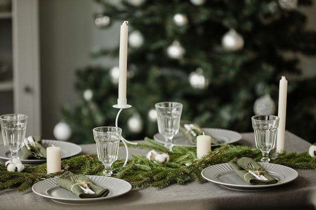 Obraz w tle stołu w jadalni ozdobionego na boże narodzenie gałązkami jodły i świecami...