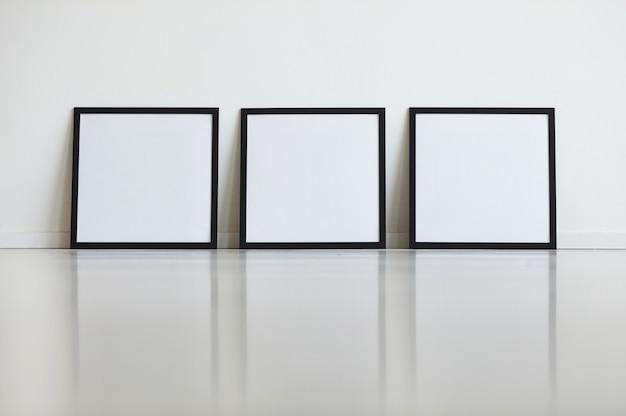 Obraz w tle trzech identycznych czarnych ramek ustawionych na białej ścianie w rzędzie w galerii sztuki,