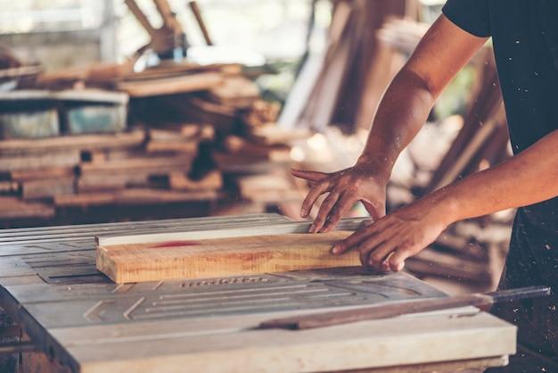 Obraz w tle warsztatu stolarskiego: stół roboczy stolarzy ze stojakiem do cięcia drewna
