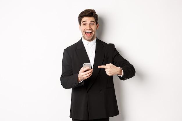 Obraz wesołego biznesmena wyglądającego na zdziwionego, wskazującego na telefon komórkowy, stojącego w garniturze na białym tle