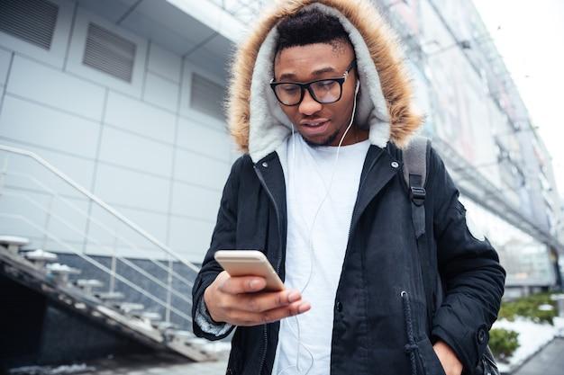 Obraz wesołego młodego mężczyzny trzymającego telefon w rękach i rozmawiającego podczas słuchania muzyki