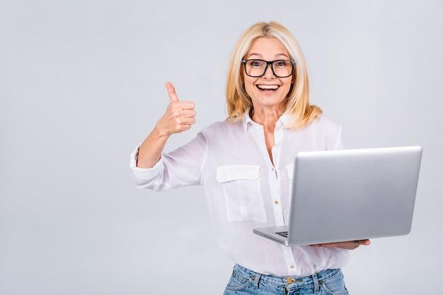 Obraz wesołej dojrzałej kobiety biznesu stojącej na białym tle nad białym tłem przy użyciu komputera przenośnego. portret u?miechni?tego starszego pani posiadania komputera typu laptop. kciuki w górę
