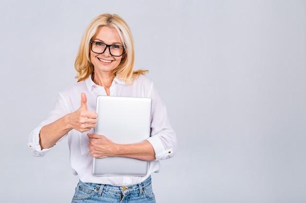 Obraz wesołej dojrzałej kobiety biznesu stojącej na białym tle nad białym tłem przy użyciu komputera przenośnego. portret u?miechni?tego starszego pani posiadania komputera typu laptop. kciuki w górę.
