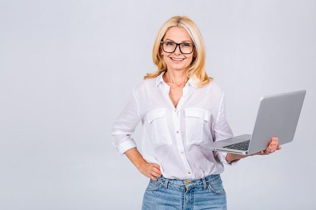 Obraz wesołej dojrzałej kobiety biznesu stojącej na białym tle nad białym tłem przy użyciu komputera przenośnego. portret u?miechni?tego starszego pani posiadania komputera typu laptop.