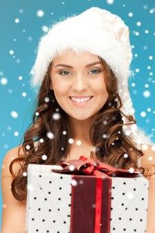 Obraz wesołej dziewczyny pomocnika świętego mikołaja z pudełkiem na prezent